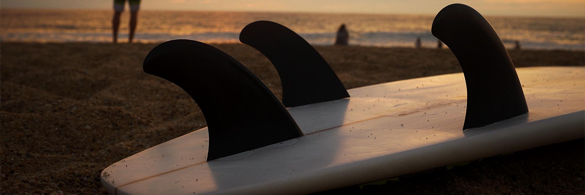 surfboard op het strand met ondergaande zon