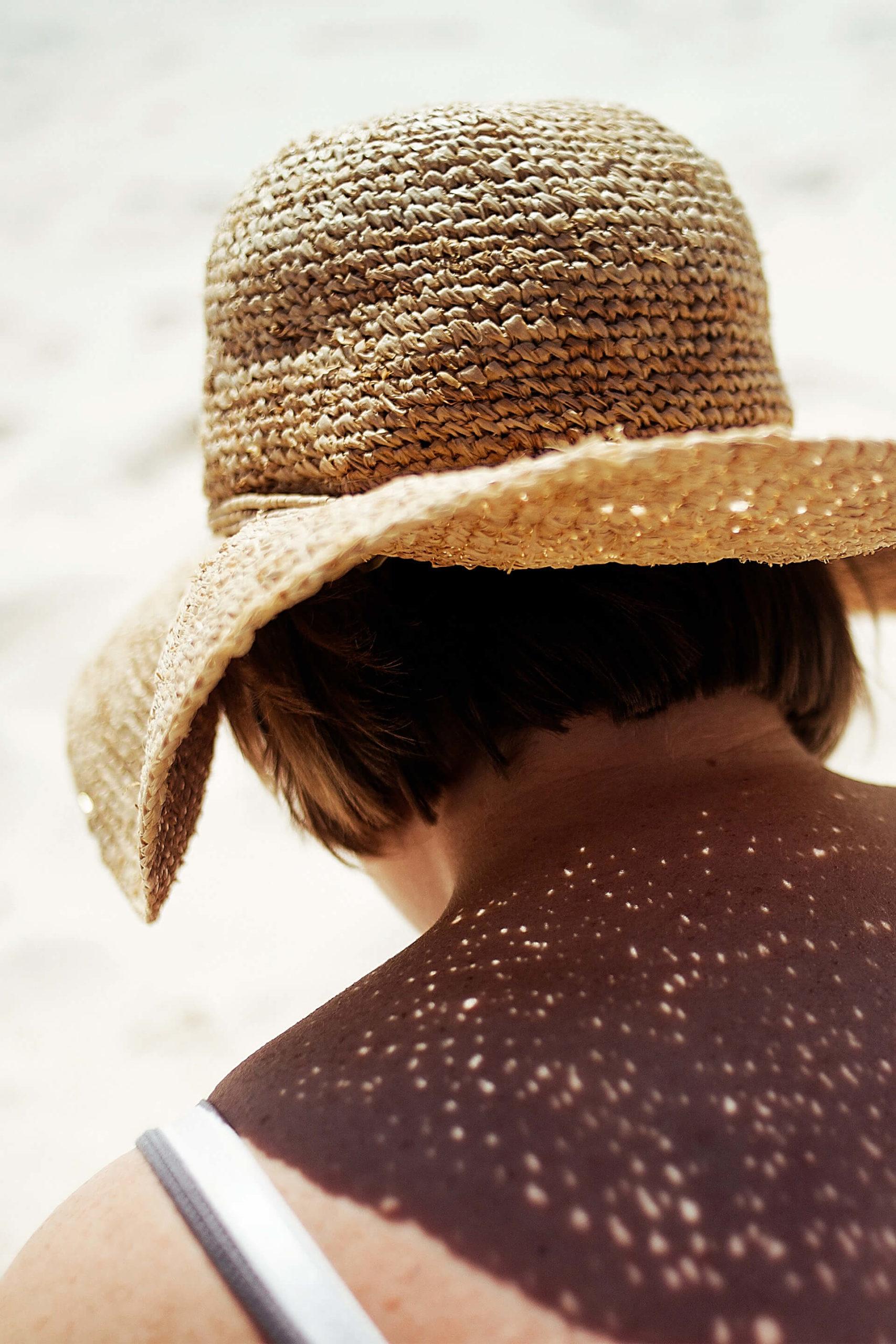 Vrouw in de zon met stro hoed en in het zand
